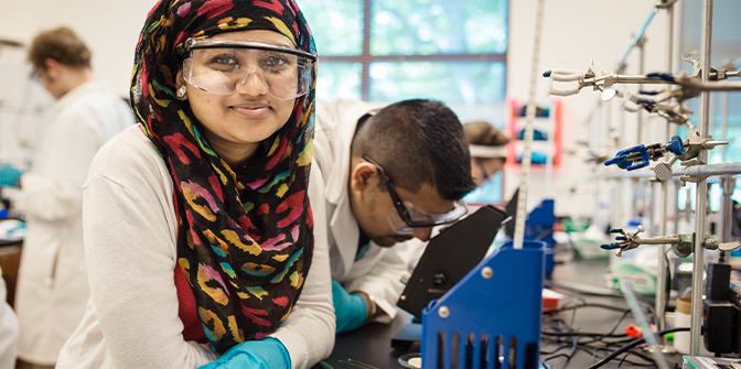 Woman in a computer science lab wearing a hijab and work goggles