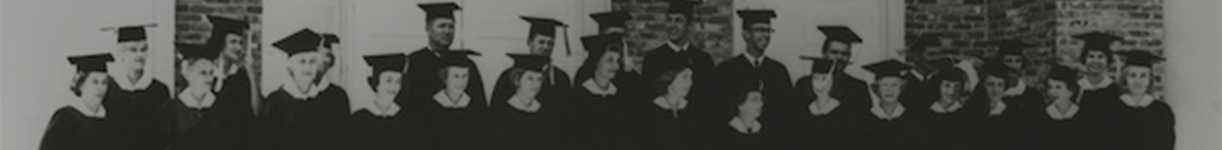 Black and white photo of about 20 people standing in cap and gown
