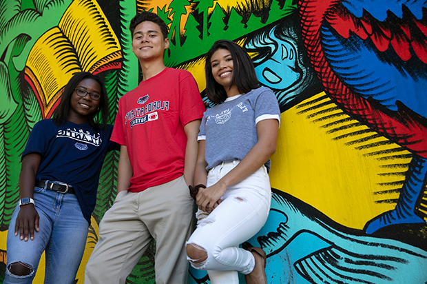 A male student and two female student lean against a wall covered with art