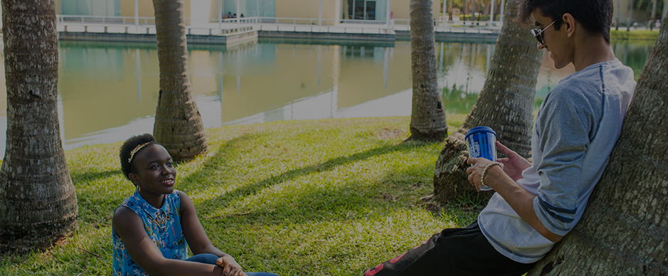 A female and male student sitting outside by a lake