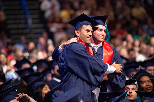 Two male student celebrate at Commencement