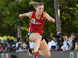 Female track member jumping over a hurdle.