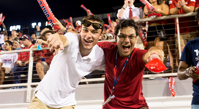 Two male 学生们 during an 澳门现金赌场 football game smiling and pointing at the camera