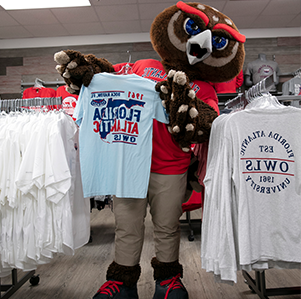 澳门现金赌场 mascot, Owlsley, holding up an 澳门现金赌场 shirt in the bookstore