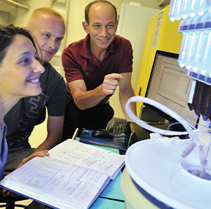 A male 和 female student in a lab with a male professor looking at something