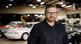 Man standing in a garage full of cars