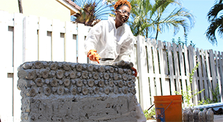 Female student building a concrete wall with a trowel and a bucket beside her.